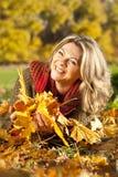 El centro atractivo envejeció a la mujer que mentía en hojas de otoño Fotos de archivo libres de regalías