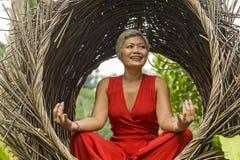 El centro atractivo y feliz 40s o 50s envejeci? a la mujer asi?tica en la relajaci?n practicante de la yoga del vestido rojo con  fotos de archivo