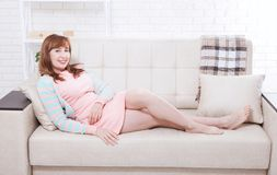 El centro atractivo y hermoso envejeció a la mujer que se sentaba en el sofá y que se relajaba en casa menopausia imagen de archivo