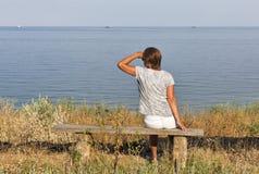 El centro blanco envejeció a la mujer que se sentaba en banco de madera con paisaje marino Imagen de archivo libre de regalías