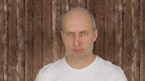 El centro calvo envejeció al hombre enojado, cerca de madera detrás almacen de video