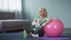 El centro cansado envejeció la relajación femenina en la estera de la yoga después del entrenamiento casero activo, disnea metrajes