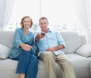 El centro contento envejeció los pares que se sentaban en el sofá que veía la TV Imagenes de archivo