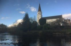 El centro de comunidad blanco de la iglesia en el río gana Imágenes de archivo libres de regalías