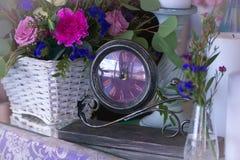 El centro de flores en una cesta adorna la tabla de la boda en pur Fotos de archivo