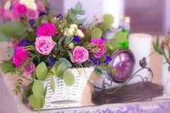 El centro de flores en una cesta adorna la tabla de la boda en pur Fotos de archivo libres de regalías
