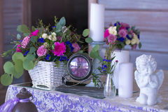 El centro de flores en una cesta adorna la tabla de la boda en pur Imágenes de archivo libres de regalías