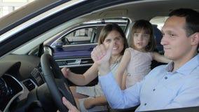 El centro de venta auto, familia alegre compró el nuevo coche en el salón del automóvil, feliz almacen de video