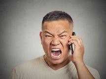 El centro enojado envejeció al empleado cabreado del hombre que gritaba mientras que en el teléfono Imagen de archivo libre de regalías