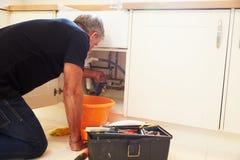 El centro envejeció al fontanero de sexo masculino que fijaba un fregadero de cocina foto de archivo libre de regalías