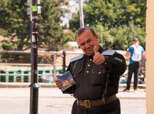 El centro envejeció al hombre caucásico en alemán sonrientes y de donantes pulgares uniformes para arriba y sostener una caja CD imagen de archivo libre de regalías