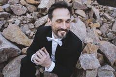 El centro envejeció al hombre que se sentaba en piedras y que sonreía con los ojos cerrados Día, al aire libre Foto de archivo libre de regalías