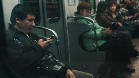 El centro envejeció al hombre que usaba el smartphone amarillo brillante que se sentaba en trai móvil del metro almacen de video