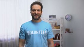 El centro envejeció al voluntario masculino que miraba a la cámara, organización de la caridad, cuidador almacen de metraje de vídeo