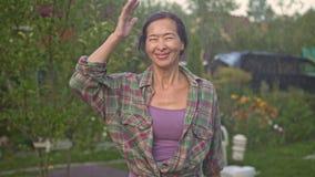 El centro envejeció a la mujer asiática que corría debajo de la lluvia en su yarda de la casa de campo almacen de video