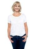El centro envejeció a la mujer en ropa de moda que sonreía en usted imagen de archivo