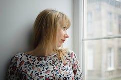 El centro envejeci? la situaci?n rubia de la mujer al lado de ventana en su?ter y parecer emotivo y pensativo imagen de archivo
