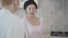El centro envejeció a las mujeres maduras que comunicaban la charla en la cocina en casa Señora que cuenta historia a sus amigos  metrajes