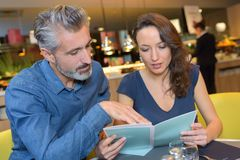 El centro envejeció los pares que miraban el menú en restaurante imagenes de archivo