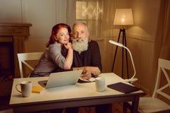 El centro envejeció los pares que se sentaban en la tabla cerca del ordenador portátil fotos de archivo