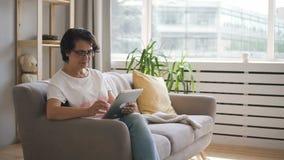 El centro envejeció el web de la ojeada de la mujer, usando la tableta, sentándose en el sofá en el apartamento almacen de video
