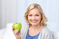 El centro feliz envejeció a la mujer con la manzana verde en casa Imagen de archivo libre de regalías