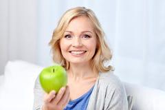 El centro feliz envejeció a la mujer con la manzana verde en casa Imágenes de archivo libres de regalías