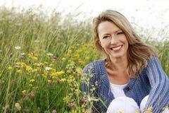 El centro feliz envejeció a la mujer en campo de flor salvaje Fotos de archivo