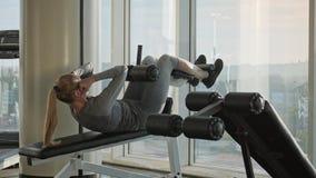 El centro hermoso deportivo envejeció a la mujer que hacía los ejercicios para los ABS almacen de metraje de vídeo