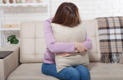 El centro hermoso envejeció a la mujer morena que sostenía una almohada y que lloraba en el sofá Fondo casero Tiempo de la menopa imagen de archivo libre de regalías