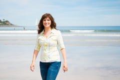 El centro hermoso envejeció a la mujer que caminaba en la playa Fotografía de archivo