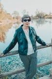 El centro hisp?nico precioso envejeci? a la mujer en el parque del lago en la puesta del sol imagenes de archivo