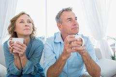 El centro pensativo envejeció los pares que se sentaban en el sofá que comía café Imagen de archivo