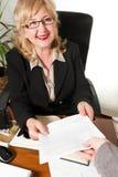 El centro sonriente envejeció a la empresaria, con el documento en sus manos. Imagen de archivo libre de regalías