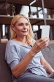el centro sonriente envejeció a la mujer en música que escuchaba de los auriculares con smartphone fotografía de archivo