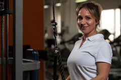 El centro sonriente feliz envejeció a la mujer que se resolvía en gimnasio Foto de archivo