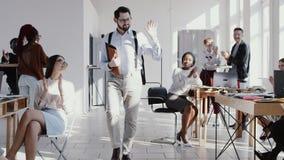 El CEO caucásico joven acertado del varón entra en la oficina moderna, palmada del equipo a él después de EPOPEYA ROJA de la cáma almacen de metraje de vídeo