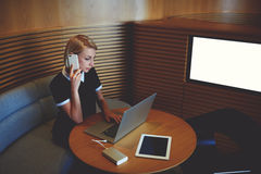 El CEO confiado de la hembra está llamando vía el teléfono de célula, mientras que se está sentando cerca de la pantalla con mofa Imagen de archivo