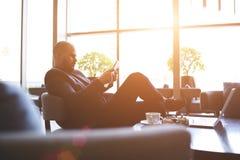 El CEO orgulloso masculino está utilizando la tableta digital, mientras que está esperando al socio en barra fotos de archivo libres de regalías