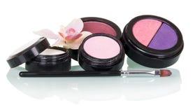 El cepillo cosmético para el maquillaje, sombra de ojos, se ruboriza y flor de la orquídea aislada en blanco imagenes de archivo