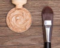 El cepillo del maquillaje con la fundación líquida exprimió fuera del tubo Imágenes de archivo libres de regalías