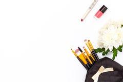 El cepillo del maquillaje en el maquillaje, el lápiz labial rojo, el esmalte de uñas rosado y un crisantemo florecen en un fondo  Imágenes de archivo libres de regalías
