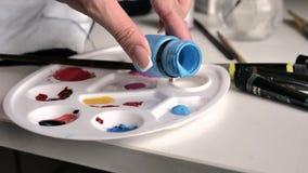 El cepillo femenino de las clavadas de la mano en pintura azul en la paleta, después la mezcla con blanco