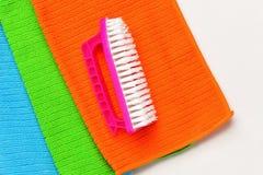 El cepillo miente en tres toallas coloreadas en un fondo blanco imagen de archivo