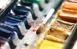 El cepillo para las mentiras de dibujo entre las cubetas con la pintura de la acuarela imagen de archivo libre de regalías