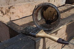 El cepillo para pintar alquitrán o el betún negro de carbón en la superficie de la terraza para impermeabilizar Imagen de archivo