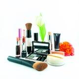El cepillo y los cosméticos del maquillaje fijaron en un fondo blanco Fotos de archivo libres de regalías
