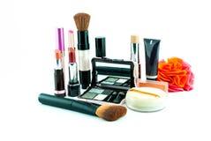 El cepillo y los cosméticos del maquillaje fijaron en un fondo blanco Fotografía de archivo libre de regalías