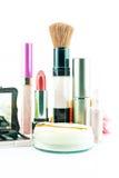 El cepillo y los cosméticos del maquillaje fijaron en un fondo blanco Imágenes de archivo libres de regalías