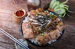 El cerdo asado a la parrilla de la rebanada con la llama del carbón de leña fijó en el cuenco de arroz en Japón fotografía de archivo